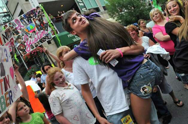 "Mike Lounello, remote coordinator with FLY 92.3, gets a big hug from Amanda Arnold, age 16 of Ravena, one of the winners of ""the best sign"" contest in front of the Times Union Center before seeing  Justin Bieber in Albany, NY on August 25, 2010. The radio station FLY 92.3 was giving away upgraded seats for the best sign. Mike is looking up at his co-workers who were judging the contest from a roof top. (Lori Van Buren / Times Union) Photo: Lori Van Buren"