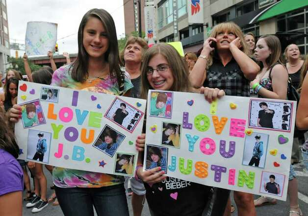 "From left, fans Leah Dollard and Gia Rotundo, both age 12 of Albany, hold up the signs they made in hopes of winning ""the best sign"" contest in front of the Times Union Center before seeing  Justin Bieber in Albany, NY on August 25, 2010. The radio station FLY 92.3 was giving away upgraded seats for the best sign. (Lori Van Buren / Times Union) Photo: Lori Van Buren"