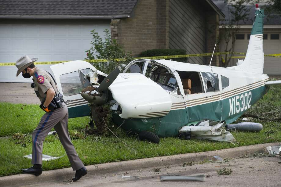 Law enforcement officers work the scene of a small aircraft crash in the front yard of a home in the 15700 block of Boulder Oaks Drive on Tuesday, July 28, 2020 in Houston. The plane crashed just before 2 a.m. Tuesday, according to reports. The pilot and passenger were taken to the hospital following the crash. According to reports, the plane also hit a tree and a light pole before stopping in the front yard of the home. Photo: Brett Coomer/Staff Photographer / © 2020 Houston Chronicle