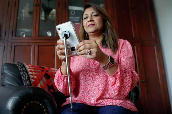 """Atiya Syverson, a workplace ergonomics consultant, demonstrates her smart phone adapter invention, the """"NEKTEKSAVR"""", to help relieve """"text neck"""" Tuesday, Jul. 14, 2020 at her home in Katy, TX. The multi-use phone attachment improves posture and neck pain while using a smart phone."""