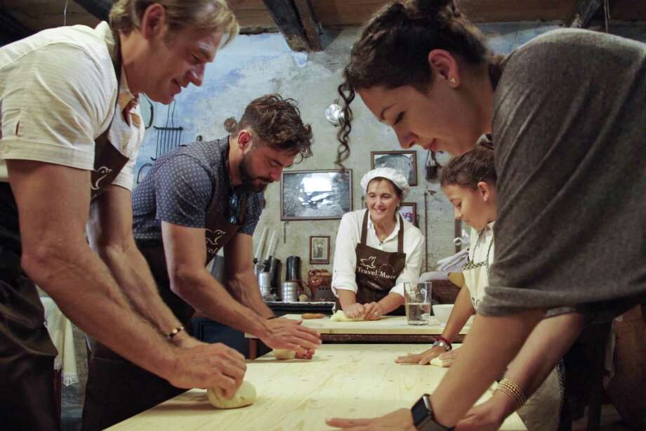 Darin Olien, left, rolls out dough with Zac Efron, second from left, as they learn about how to make the breads and pasta of Sardinia, an area of Italy known for its large population of residents over the age of 100. Photo: Netflix / Contributed Photo / Courtesy Of Netflix / ©2020 Netflix, Inc.