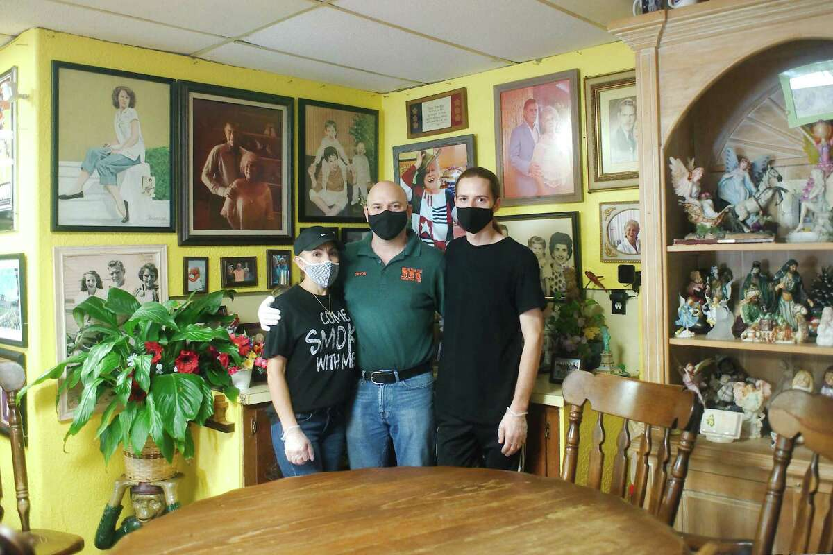 Surrounded by vintage family photographs, Central Texas Bar-B-Q owner Devon Nixon stands with wife Elvia and son Jude in what is affectionately called the