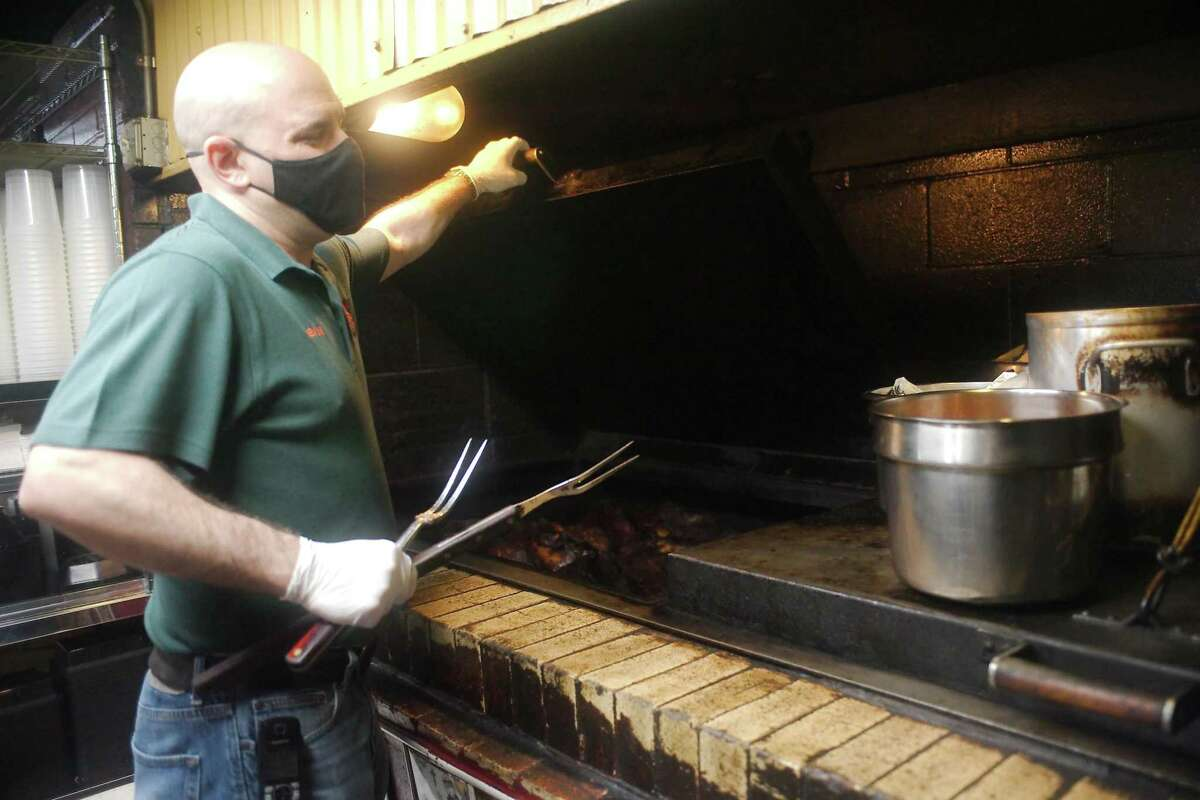 Owner Devon Nixon lifts the lid on one of the pits used to cook brisket at Central Texas Bar-B-Q in Pearland.