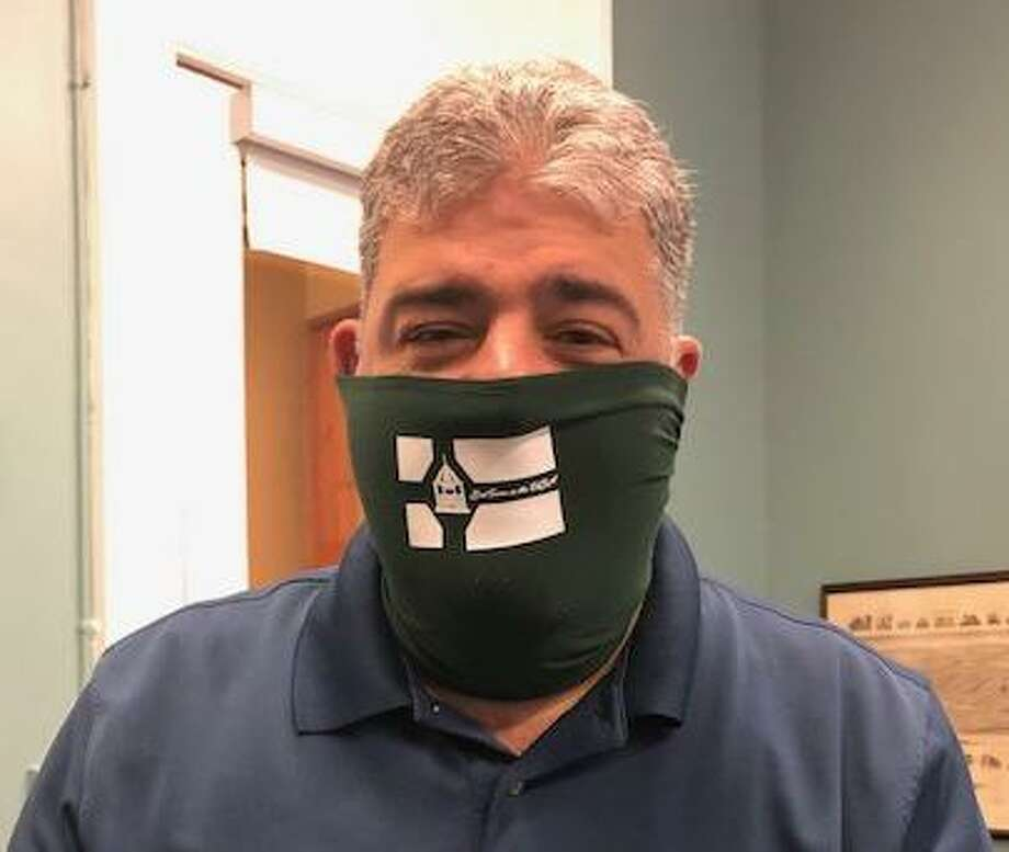 New Milford Mayor Pete Bass wears one of the masks his office is selling to raise money to purchase more PPE for seniors in town. Photo: Contributed Photo /