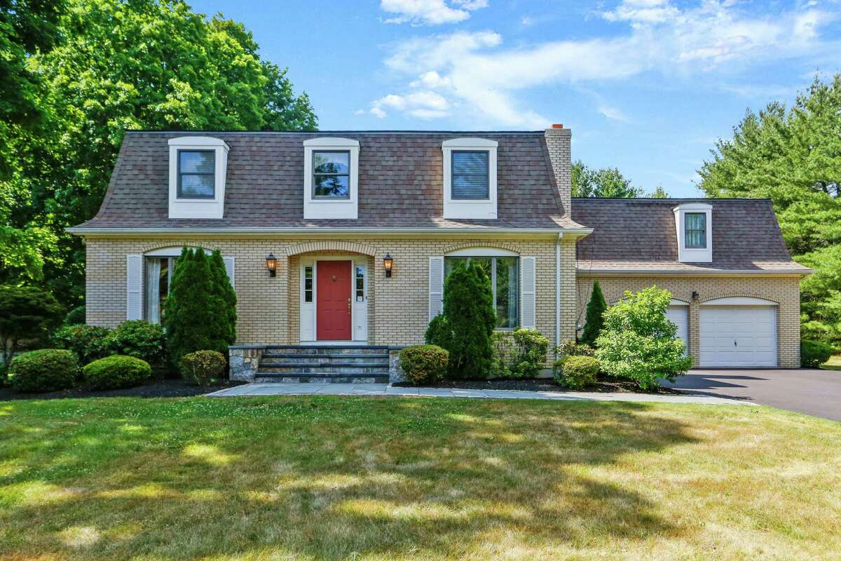 The yellow brick colonial house at 6 Ridgeway Road in Easton has a distinguished mansard wood shingle roof.