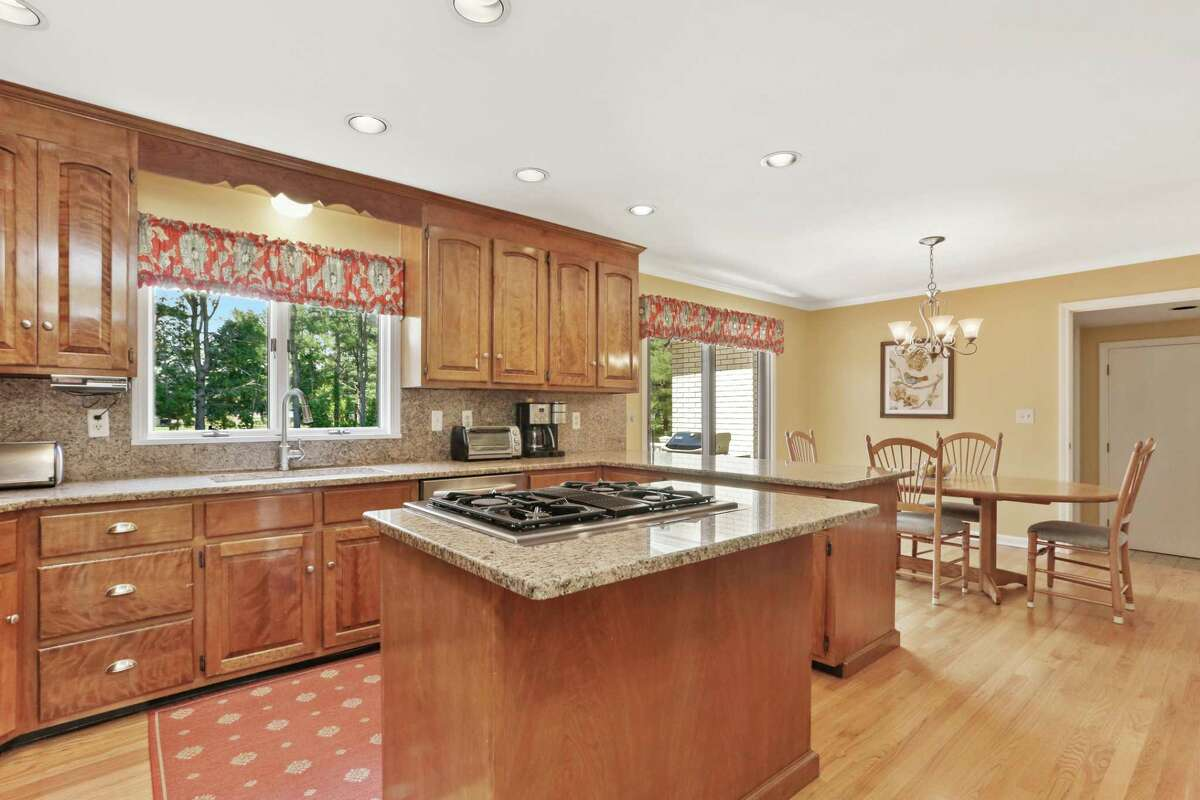 In the kitchen there is a small center island, granite counters, quite a few cabinets, and stainless steel appliances.