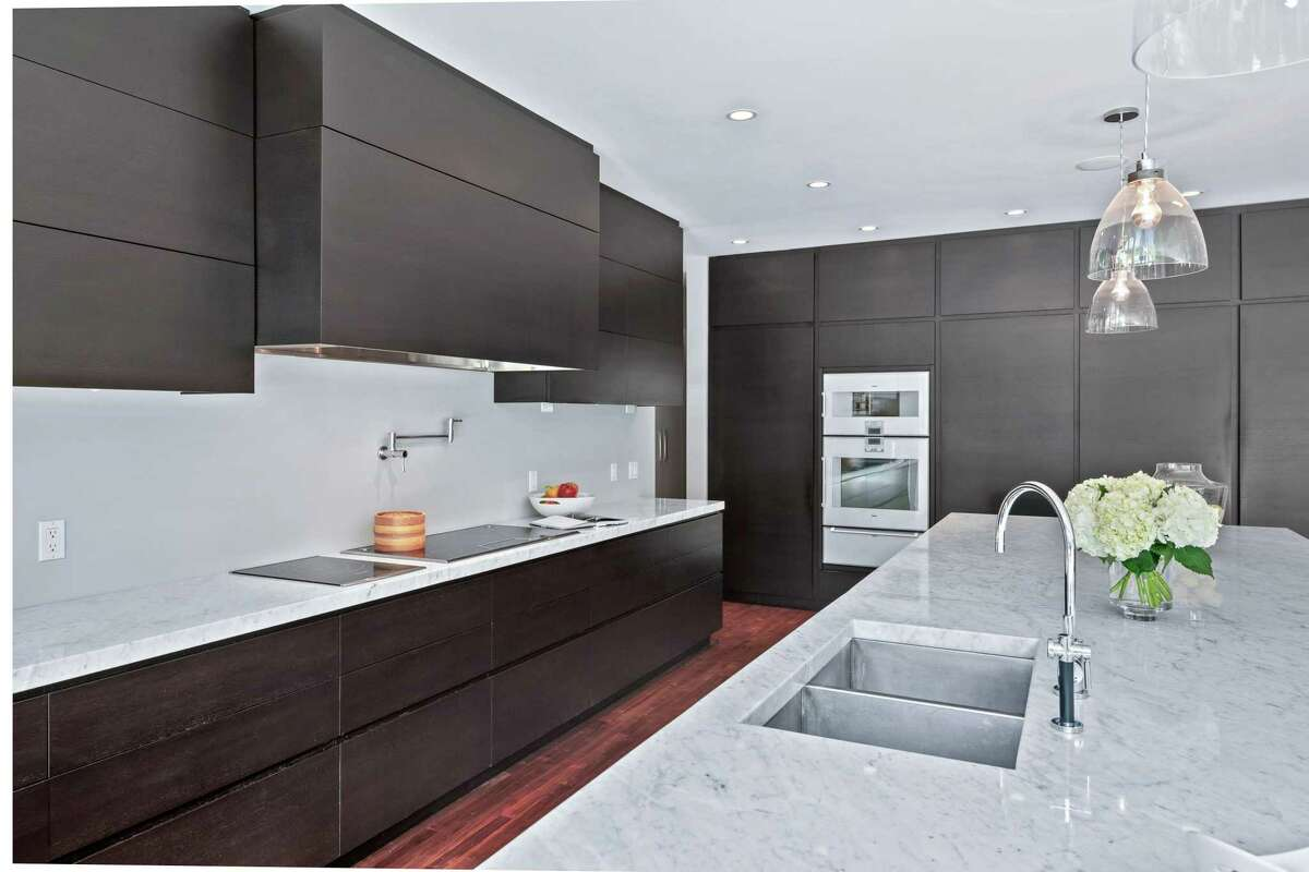 The massive, modern gourmet eat-in kitchen features a 16-foot center island/breakfast bar, quartzite counters, large wine refrigerator, a pot-filler, walk-in pantry, and Gaggenau and Thermador appliances.