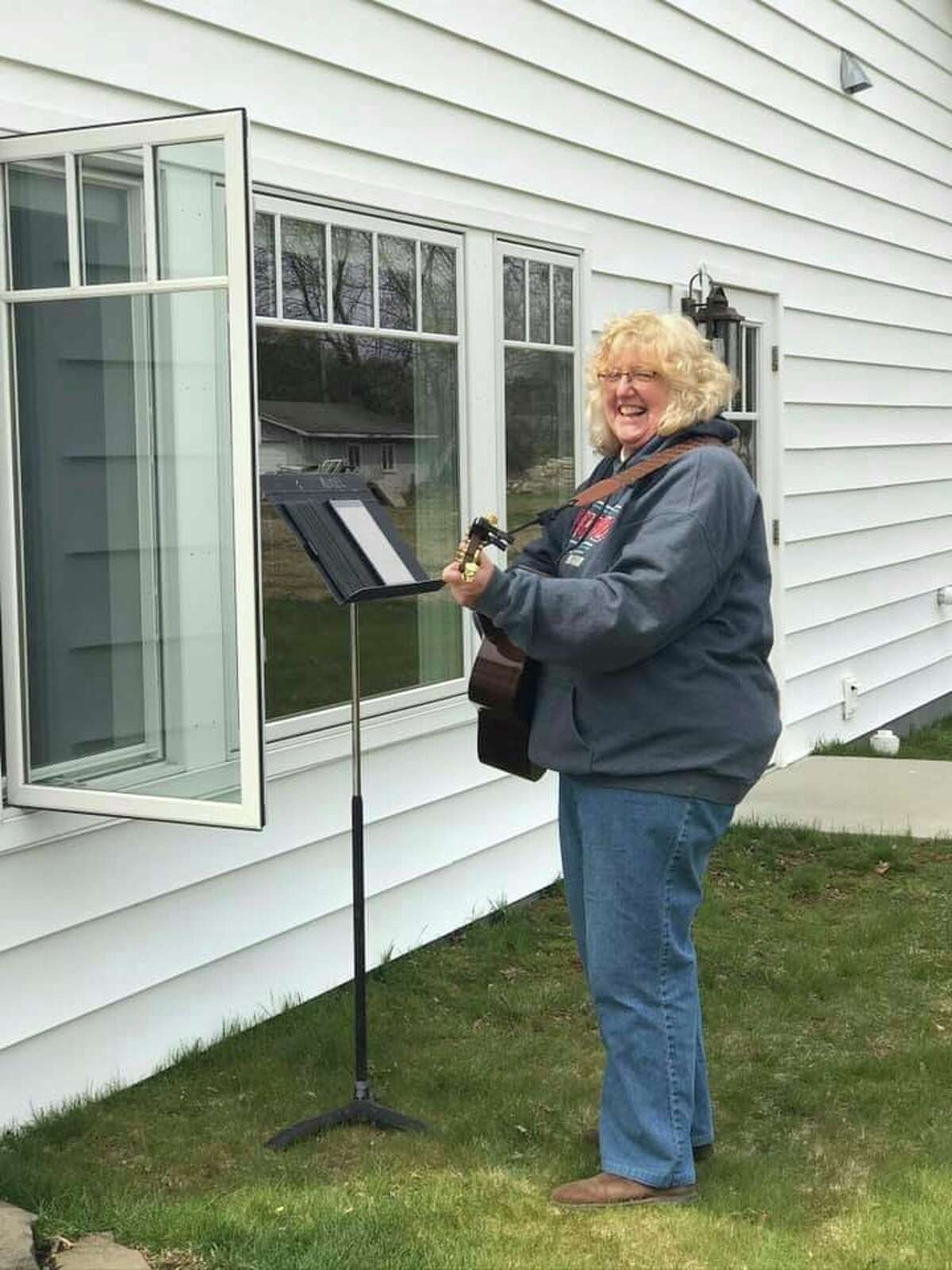 Due to coronavirus precautions, Kris Kuziel of Port Austin sings outside of Questover Assisted Livingwhereresidents can listen through open windows or from the patio when the weather is nice. (Questover/Courtesy Photo)