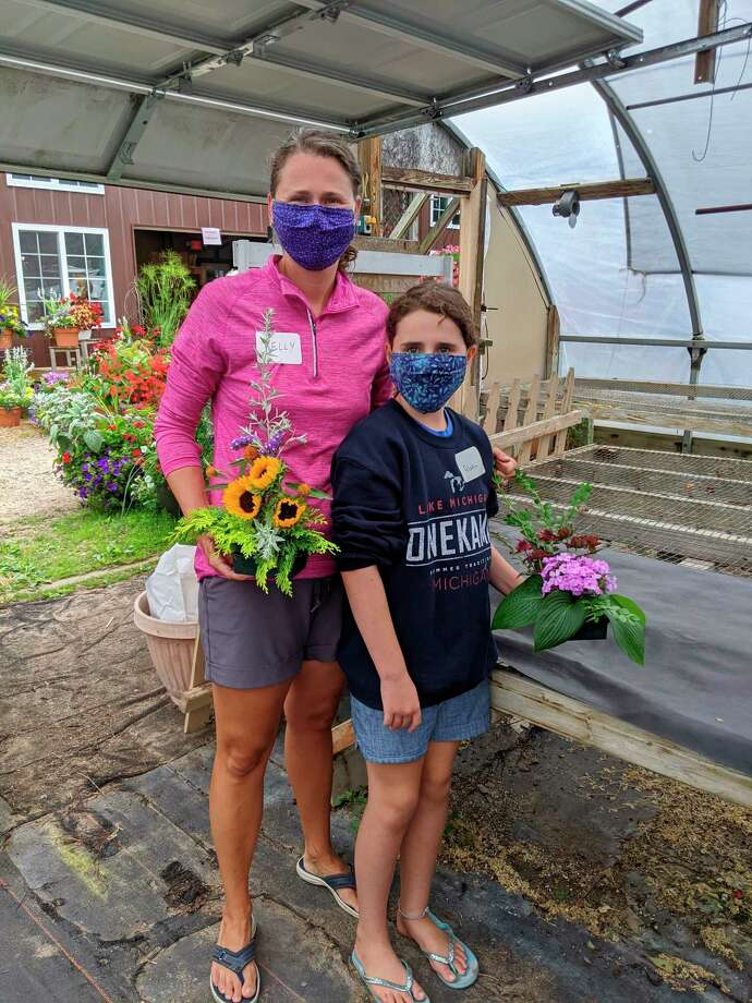 Kelly and Aleta McQueen, visiting Onekama from Virginia, hold their floral designs on July 22. The family worked with the Portage Lake Garden Club to create simple line mass designs in shallow containers. (Courtesy photo)