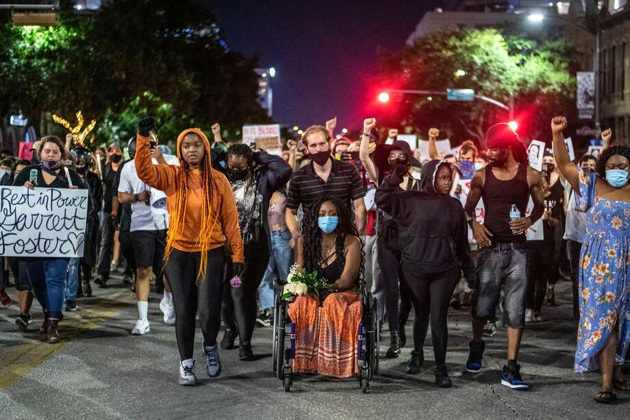 Whitney Mitchell, Garrett Foster's fiancÃe, attends a march for Foster on July 26, 2020 in downtown Austin. Foster, 28, who was armed and participating in a Black Lives Matter protest, was shot and killed after a chaotic altercation with a motorist who allegedly drove into the crowd. The suspect, who has yet to be identified, was taken into custody. Photo: Sergio Flores/Getty Images / 2020 Getty Images