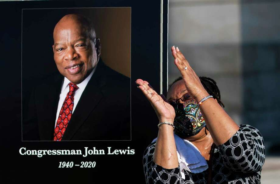 Jaquenette Ferguson from Oxon Hill, Md., gestures as she gets her picture taken beside a portrait of the late Rep. John Lewis, D-Ga., near the East Front Steps of the U.S. the Capitol, Tuesday, July 28, 2020, in Washington. Photo: Manuel Balce Ceneta, AP / Copyright 2020 The Associated Press. All rights reserved.