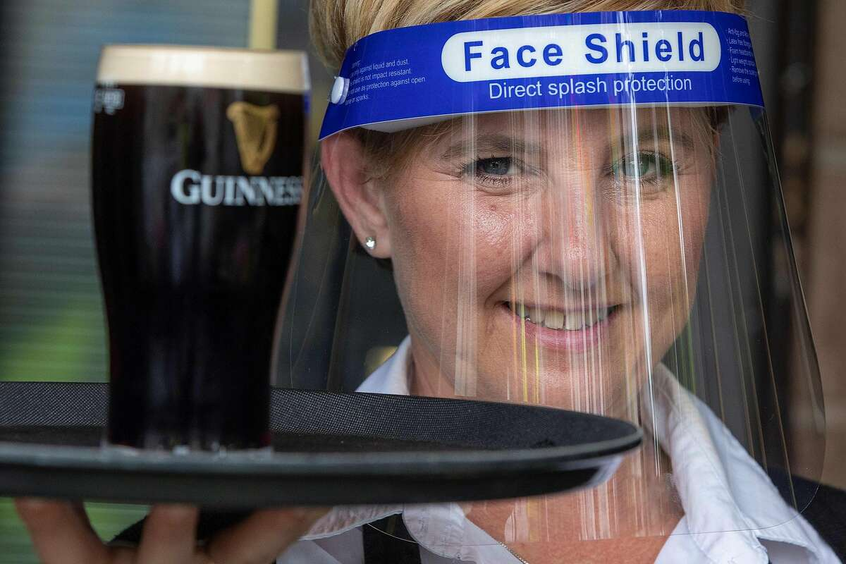 FILE - An employee of Murray's Bar in Dublin, Ireland, wears a face shield as a precautionary measure against spreading COVID-19.