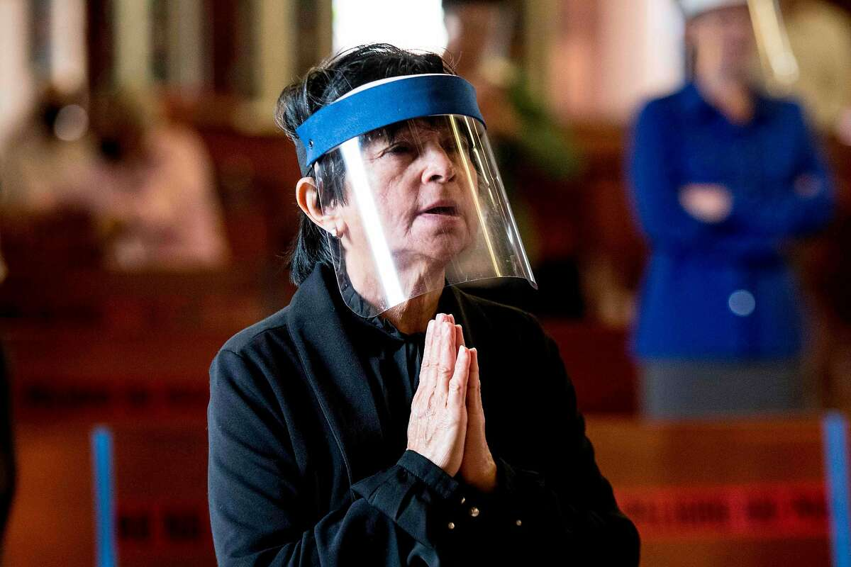 FILE - A woman protected by a face shield against COVID-19 prays at the Basilica de los Angeles in Cartago, Costa Rica.