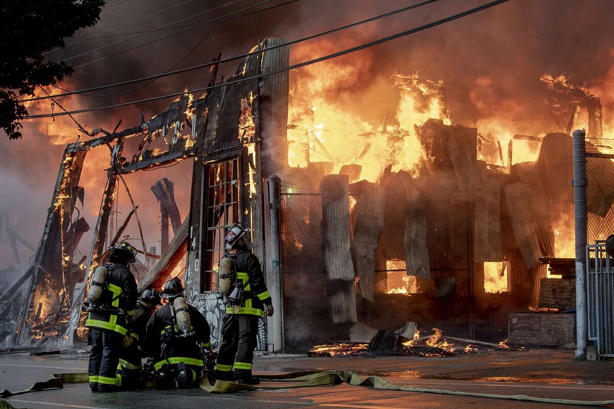 Firefighters battle a fire Tuesday, July 28, 2020, in the South of Market neighborhood of San Francisco. About 150 firefighters battled a massive blaze that raged through three buildings, sending a thick, black plume of smoke up to the sky and embers to a nearby freeway. (Karl Mondon/Bay Area News Group via AP)