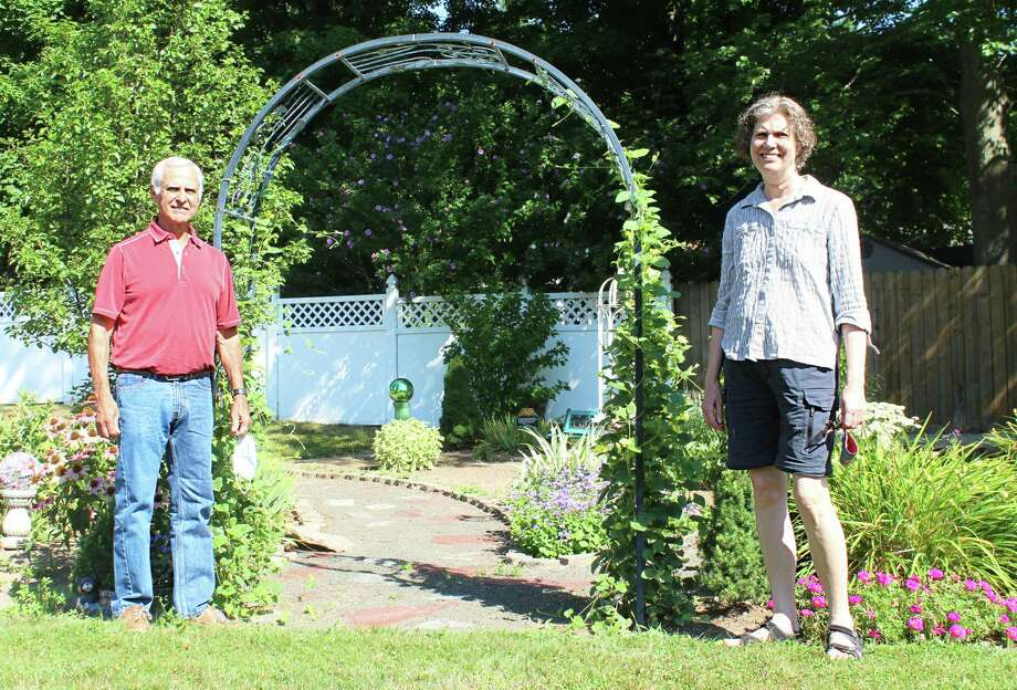 Third Congregational Church president Fred Shiffer, left, and the Rev. Nancy Lois stand in the butterfly garden at the rear of the property at 94 Miner Street. Four weeks ago, due to the coronavirus, church leaders erected a large tent on the grounds so parishioners have the option of enjoying services outside, as well as on the web. Photo: Cassandra Day / Hearst Connecticut Media