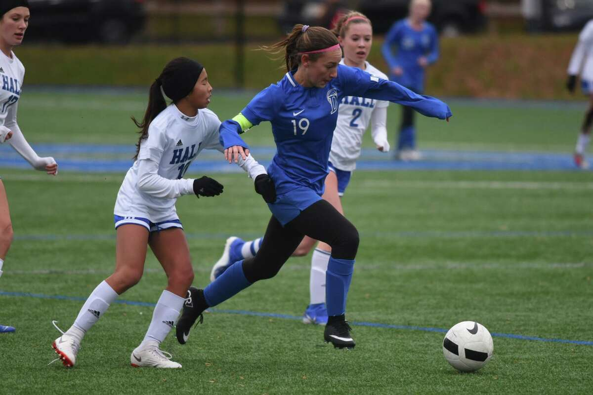 Darien's Kate Bellissimo (19) gets in front of Hall's Ally Yamamoto (10) during the first round of the CIAC Class LL girls soccer tournament at Darien High School on Tuesday, Nov. 12, 2019.