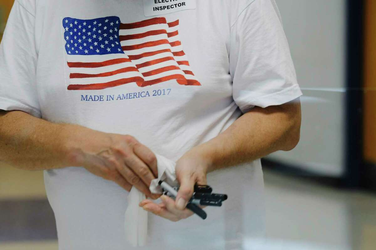 An election inspector disinfects pens for voters to use at the Rensselaer School Campus during the revote on Rensselaer City School District budget on Tuesday, July 28, 2020, in Rensselaer, N.Y. (Paul Buckowski/Times Union)