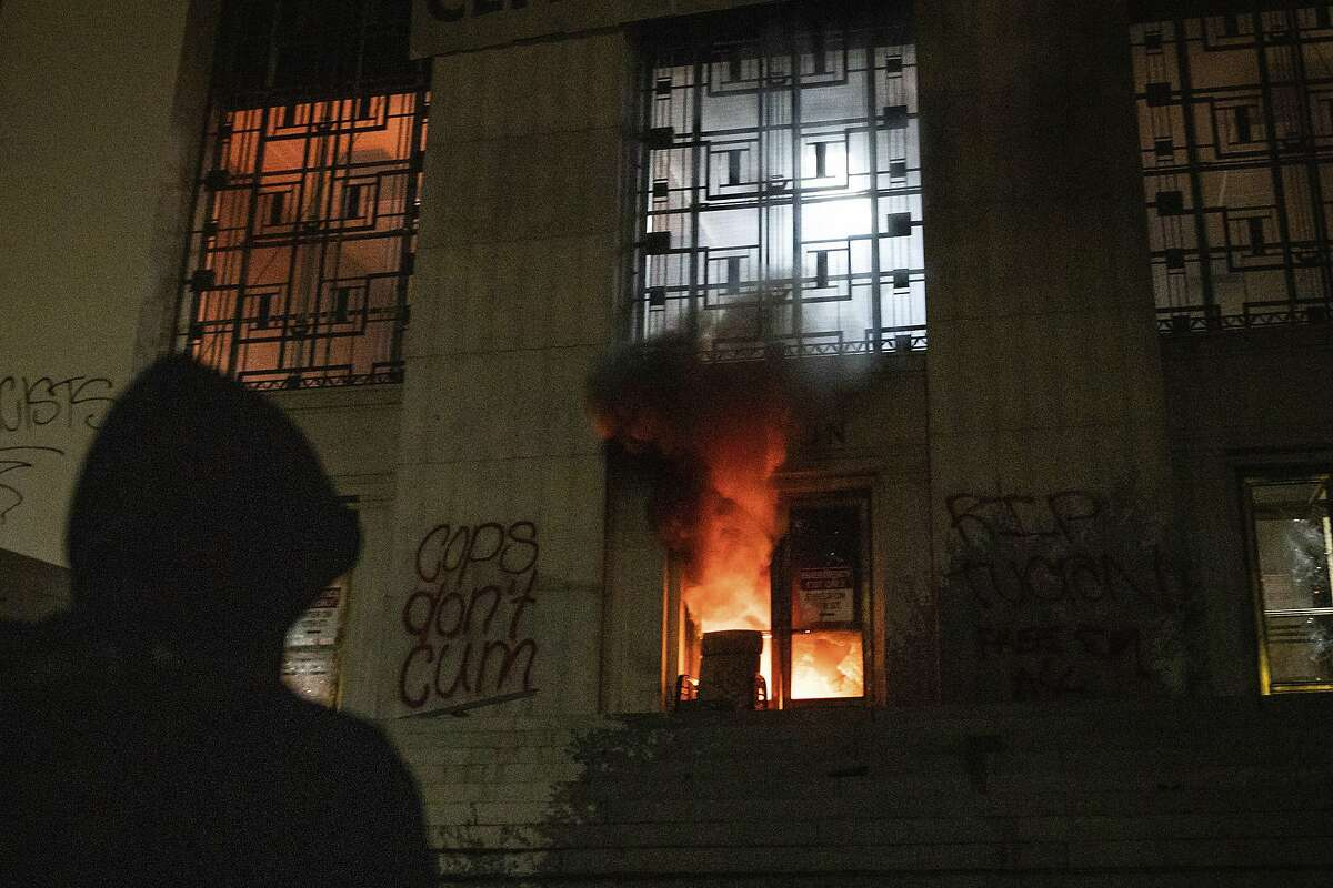 A protester watches a blaze at the entrance of the Alameda County Superior Courthouse during a protest on Saturday, July 25, 2020, in Oakland, Calif. Protesters in California set fire to the courthouse, damaged a police station and assaulted officers after a peaceful demonstration intensified late Saturday, Oakland police said. (AP Photo/Christian Monterrosa)