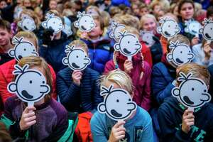 Children cover their faces with the fictional character Greg Heffley during a gathering with American cartoonist, producer and author of children's books Jeff Kinney in Norway in 2018.