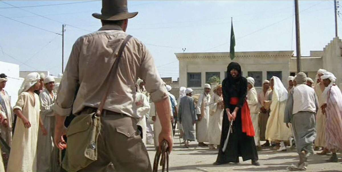 Harrison Ford (back to camera, in foreground) as Indiana Jones facing Arab Swordsman, played by Terry Richards, in