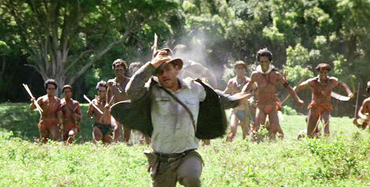 Harrison Ford as Indiana Jones being chased by weapon wielding Hovitos in