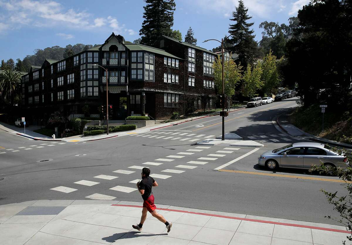 A runner passes a student housing building at UC Berkeley at the intersection of Hearst and Gayley on Tuesday, July 28, 2020, in Berkeley, Calif. Many Bay Area universities are still planning to offer on-campus housing to some of the student population in the fall, even though classes will be almost entirely online. But the residential experience is bound to be unlike any other year--UC Berkeley, for instance, plans to have students self-isolate upon arrival on campus and then remain in small social bubbles after. The revised housing plans come as cases spike in California, making the school year more uncertain.