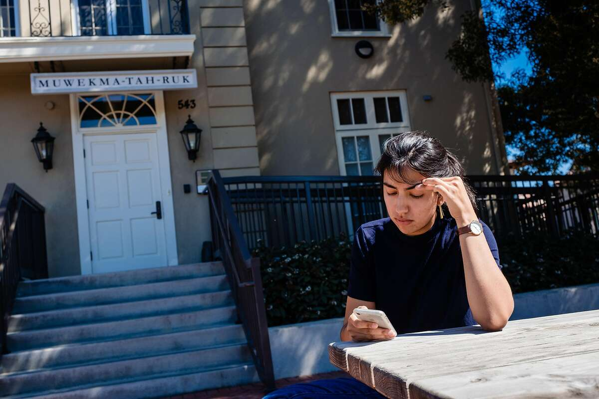 Olivia Arballo Saenz, a student at Stanford uses her phone outside of her Dorm in Palo Alto, Calif. on Thursday, March 12, 2020. Stanford students are being encouraged to move out of the dorms because of coronavirus concerns.