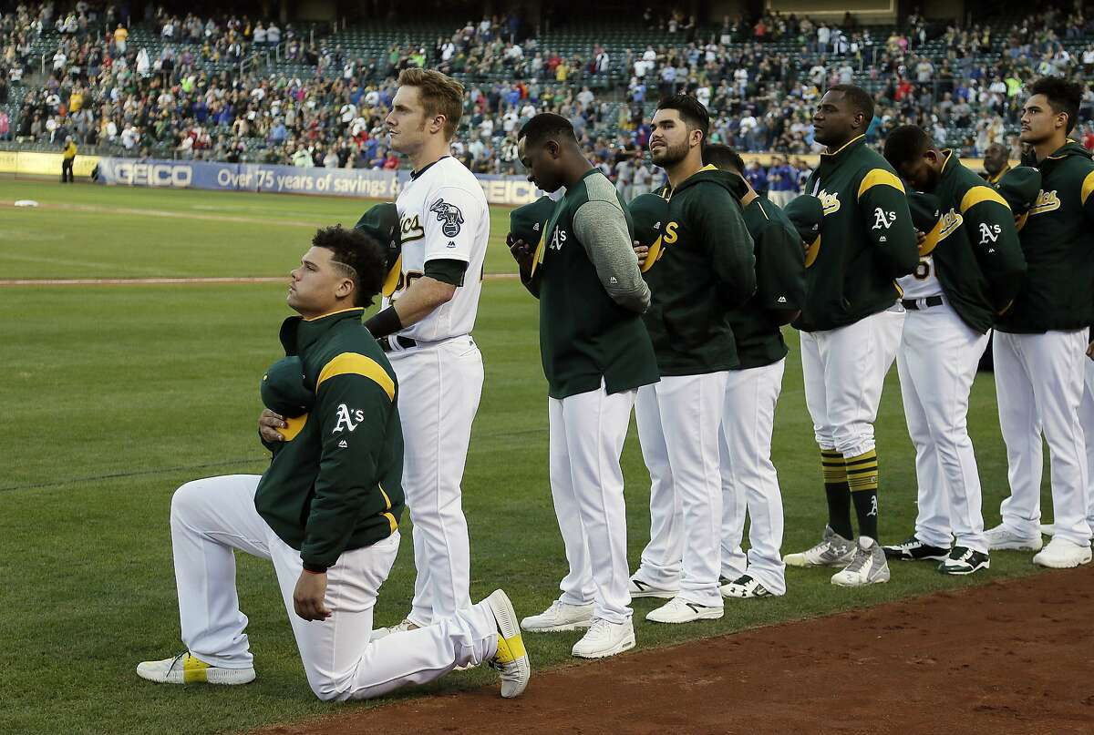 FILE - In this Sept. 23, 2017, file photo, Oakland Athletics catcher Bruce Maxwell kneels during the national anthem before the start of a baseball game against the Texas Rangers in Oakland, Calif. The New York Mets have agreed to a minor league contract with Maxwell, the first major league player to kneel during the national anthem to protest racial injustice in 2017, according to a person familiar with the deal. (AP Photo/Eric Risberg, File)