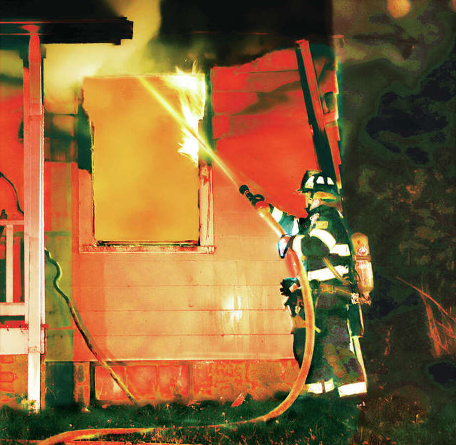 An Alton firefighter knocks down flames from a window of a small house early Tuesday morning in the 3500 block of Oscar Avenue in Alton. Alton firefighters recieved the call about 4:30 a.m. for the fire that gutted the house. A mutual aid box alarm was activated for assistance from East Alton firefighters. The Illinois State Fire Marshal's Office joined the investigation Tuesday morning. As of mid-day Tuesday the fire was still under investigation, origin unknown. No injuries were reported. Itwas an occupied house but the residents were apparently not home at the time.