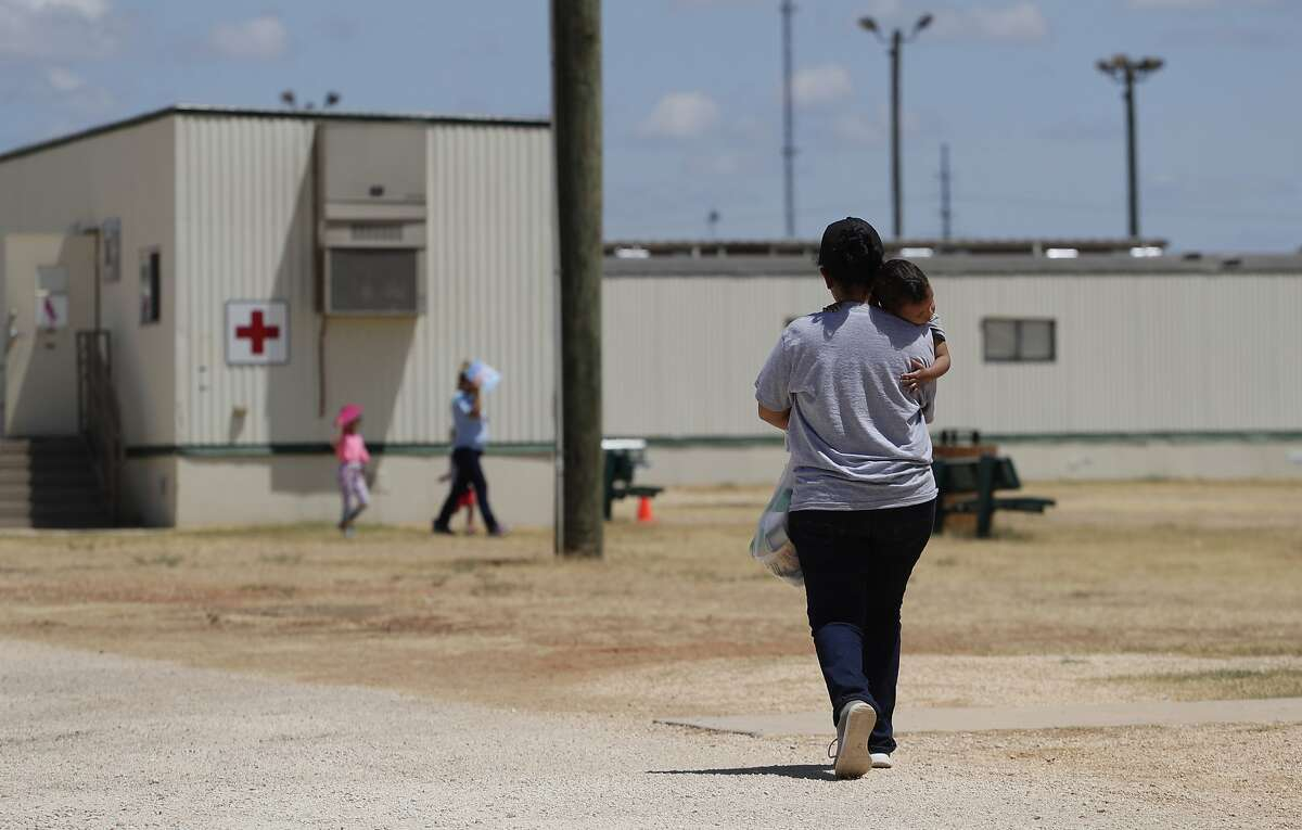 """Immigrants seeking asylum walk at the ICE South Texas Family Residential Center, Friday, Aug. 23, 2019, in Dilley, Texas. The U.S. government did not release 100 immigrant children detained with their parents despite this week's deadline set by a judge who had described family detention centers as """"on fire"""" due to the threat of the coronavirus. U.S. Immigration and Customs Enforcement said Tuesday, July 28, 2020 that it was in compliance with Judge Dolly Gee's June 26 order, which originally set a July 17 deadline for the release of all children held by ICE for more than 20 days."""