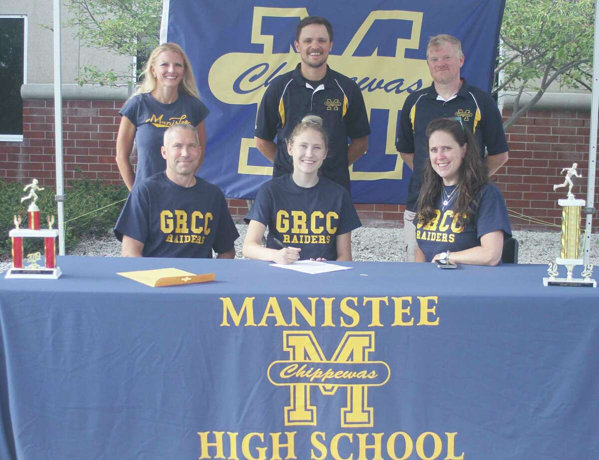 Noelle Fink signs to run cross country at Grand Rapids Community College at a recent ceremony held at Manistee High School. Fink is joined by parents James and Kellie, along with her MHS coaches Hilary Edmondson, Andy Anderson and Eric Thuemmel. (Dylan Savela/News Advocate)