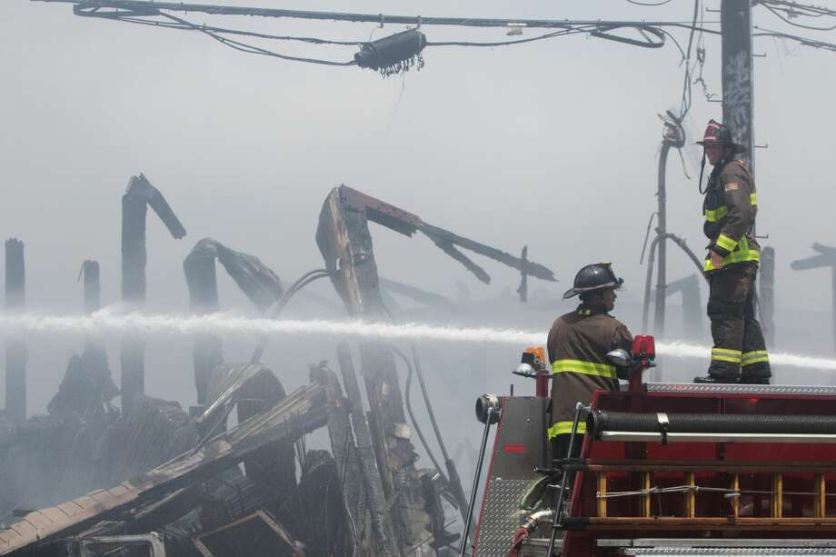 San Francisco firefighters spray down hot spots in the remains of several buildings that were engulfed in a a 5-alarm fire in San Francisco, Calif. on July 28, 2020. Photo: Douglas Zimmerman/SFGATE / SFGATE