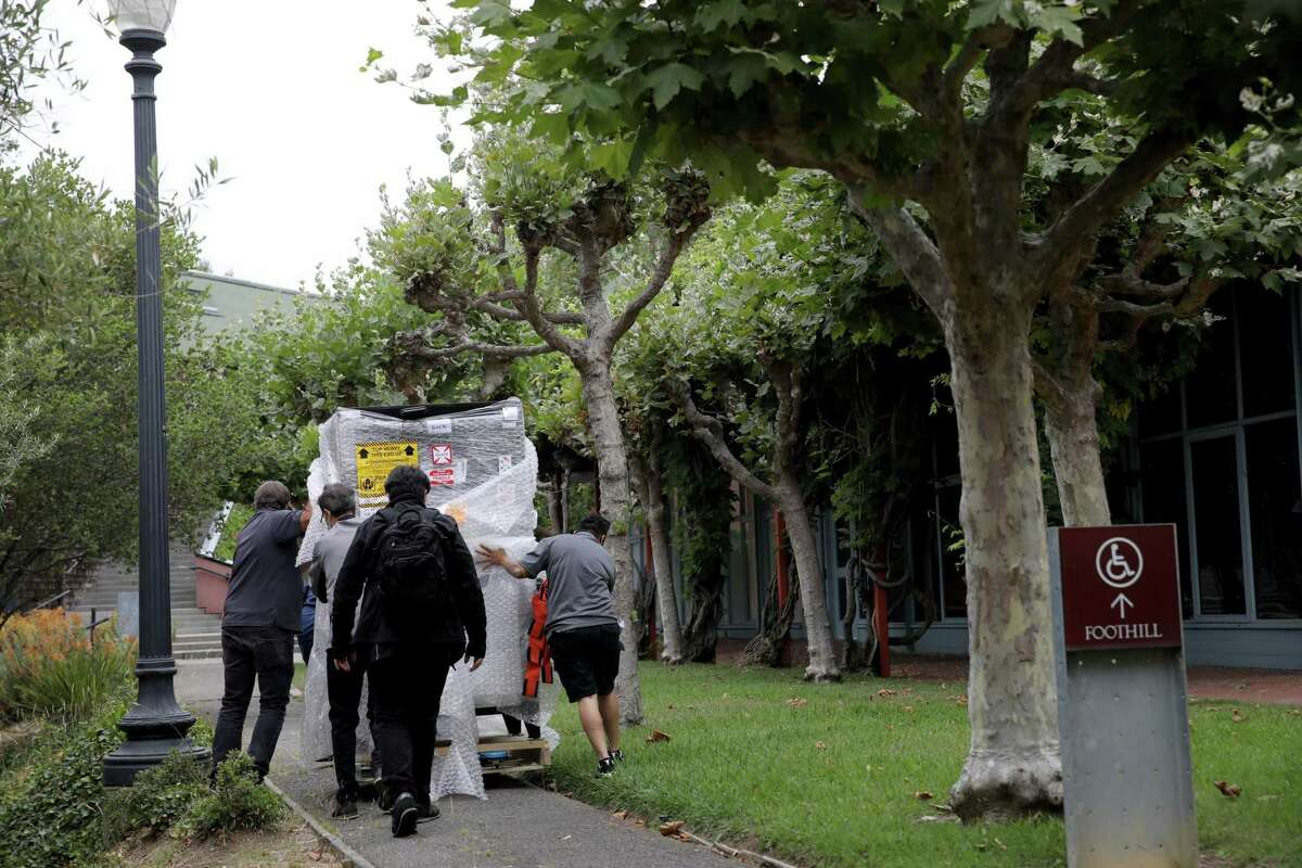 Workers move items to Foothill Residence Hall at UC Berkeley in July. An outbreak on campus has prompted sharp restrictions on student activities.