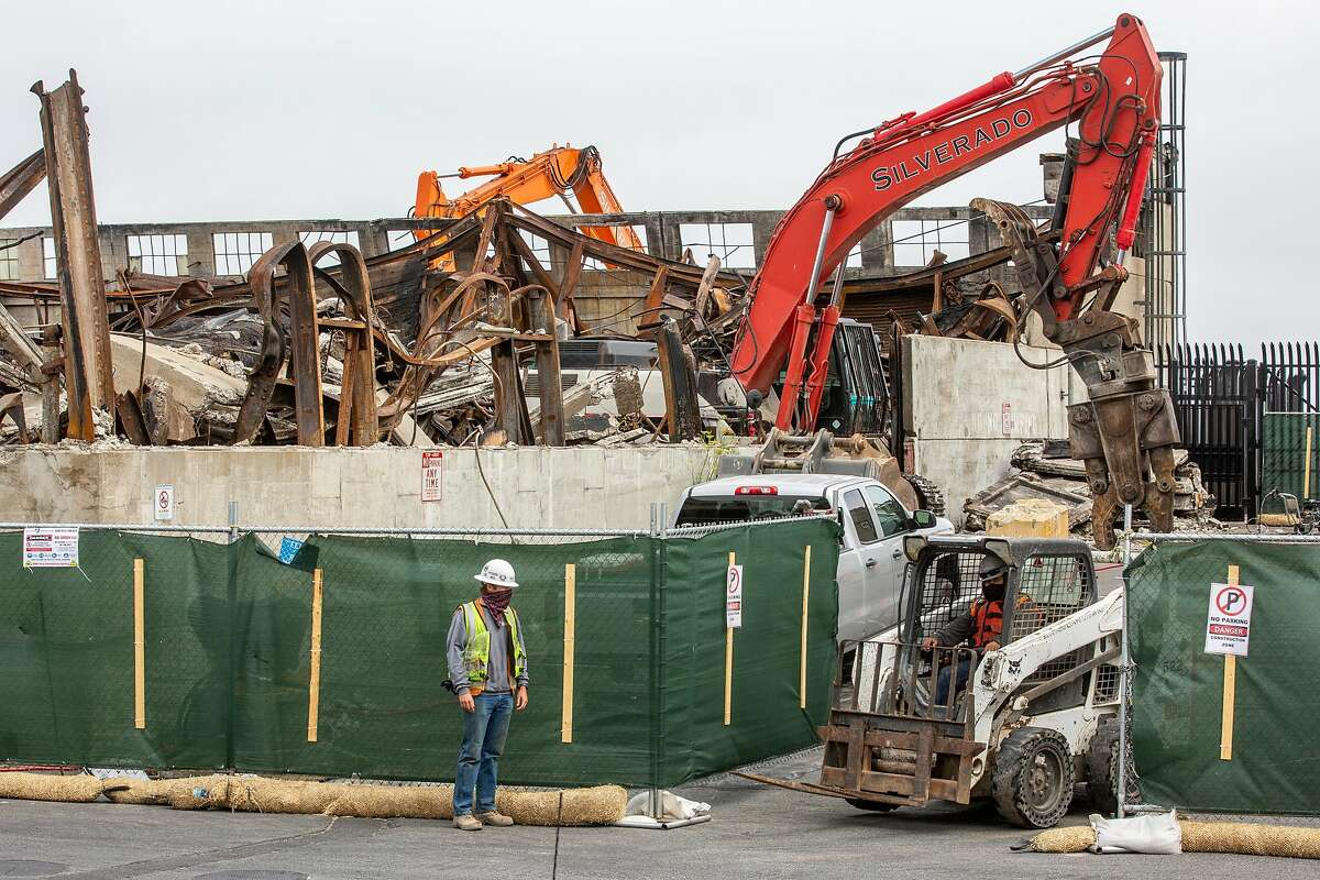 Demolition workers at Pier 45 in July. A fire on May 23 destroyed Shed C, where crabbers stored equipment. They have sued the city's port for their losses.