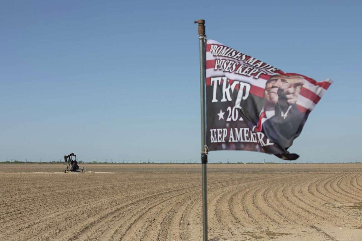 An active pump jack stands past a Trump 2020 flag flying at a private ranch in Midland, Texas, U.S, on Thursday, April 23, 2020.