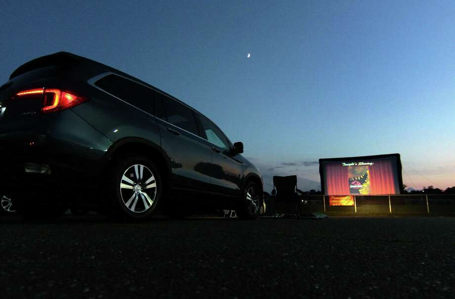 Trumbull High School's Thespian Society holds its Summer Drive-In Movie Series in the parking lot at Trumbull High School on Saturday. Saturday's feature was Jurassic Park. The next movie, The Lion King, is slated for next Saturday at 7:30 p.m. Photo: Christian Abraham / Hearst Connecticut Media / Connecticut Post