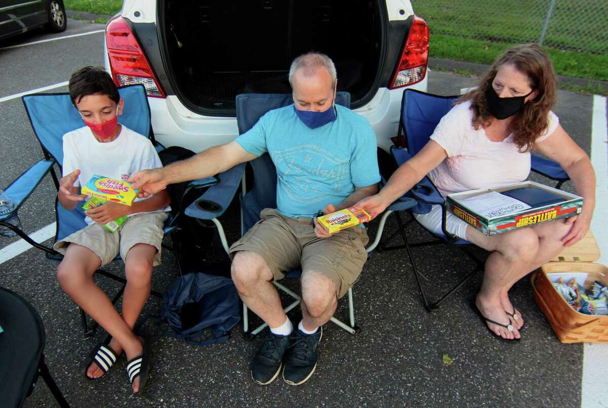 Betsy Gilberti, right, passes candy to her husband Joe and son Anthony, 12, at Trumbull High School Thespian Society's Summer Drive-In Movie Series in the parking lot at Trumbull High School in Trumbull, Conn., on Saturday July 25, 2020.