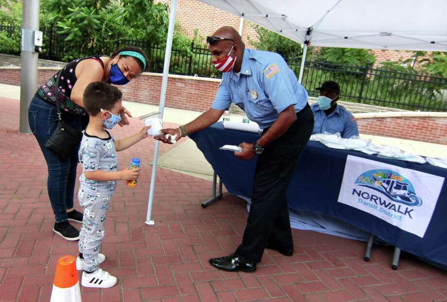 Norwalk Transit District employee Harry Arokiadass hands a mask to Aram Aguirre, 4, of Norwalk, during a mask giveaway in front of the Norwalk Transit District hub in Norwalk on Tuesday. With Aram is his mom, Maria Osorio. Photo: Christian Abraham / Hearst Connecticut Media / Connecticut Post