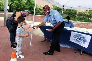 Norwalk Transit District employee Harry Arokiadass hands a mask to Aram Aguirre, 4, of Norwalk, during a mask giveaway in front of the Norwalk Transit District hub in Norwalk on Tuesday. With Aram is his mom, Maria Osorio.