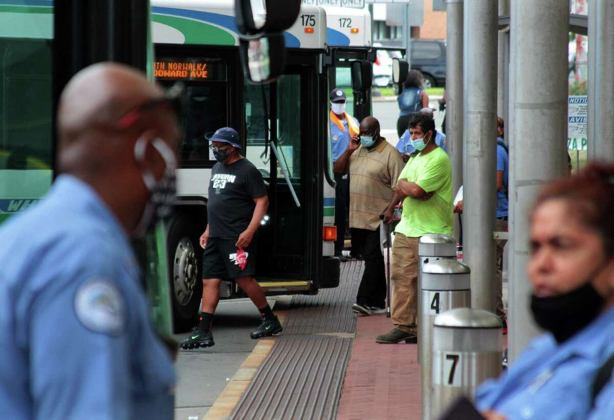 Riders wear masks as they walk to waiting buses at the Norwalk Transit District on Tuesday.