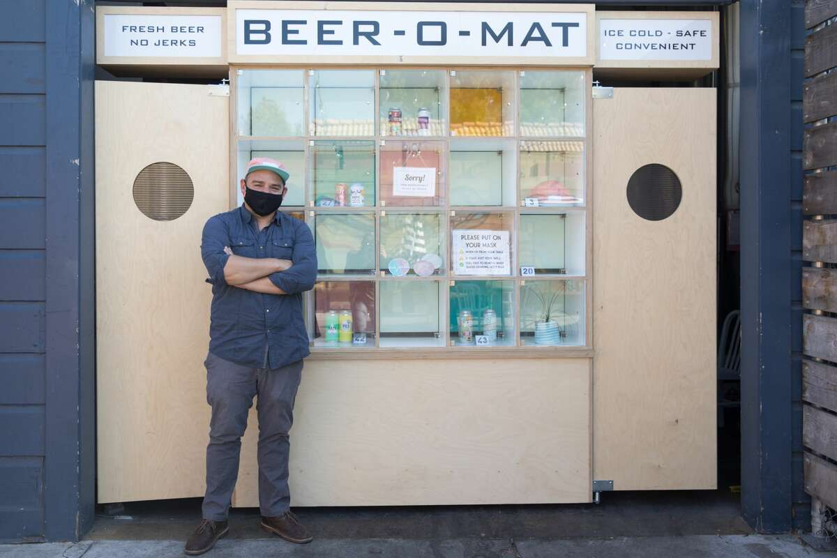 Co-owner Sam Gilbert stands in front of the BEER-O-MAT at Temescal Brewery in Oakland Calif. on July 27, 2020. Temescal Brewery is using contactless ordering and delivery system, an invention the named the BEER-O-MAT for customer orders at the outdoor beer garden in the Temescal neighborhood.