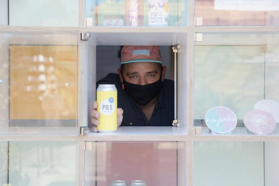 Co-owner Sam Gilbert places an order in a window of the Beer-O-Mat at Temescal Brewing in Oakland, Calif. on July 27, 2020. Photo: Douglas Zimmerman/SFGATE / SFGATE