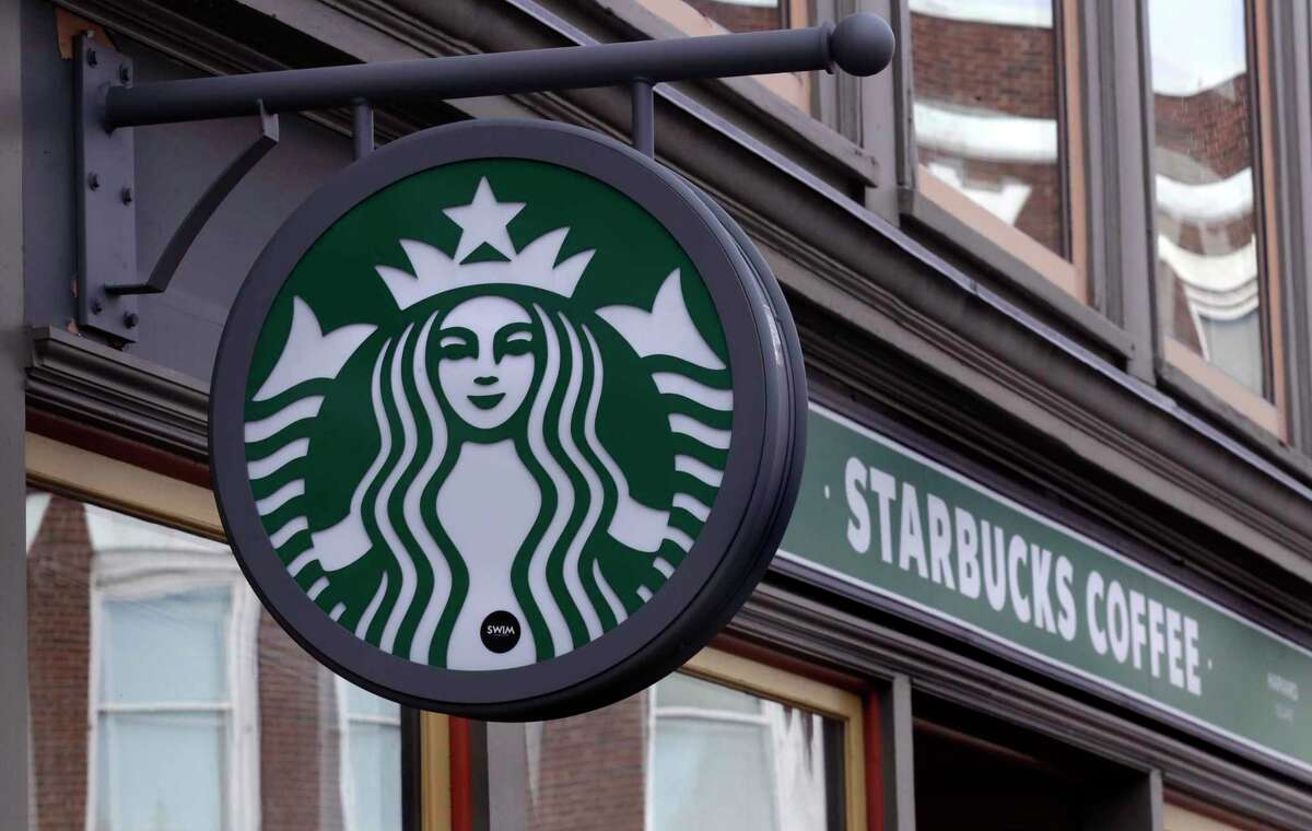 FILE- This Dec. 13, 2018, file photo shows a sign for a Starbucks Coffee shop in Harvard Square in Cambridge, Mass. Starbucks says ita€™s seeing steady recovery as its stores reopen, but it expects the impact of the new coronavirus to last well into the fall. The coffee giant said Tuesday, July 28, 2020 that revenue in its fiscal third quarter plummeted 38% to $4.2 billion. (AP Photo/Charles Krupa, File)