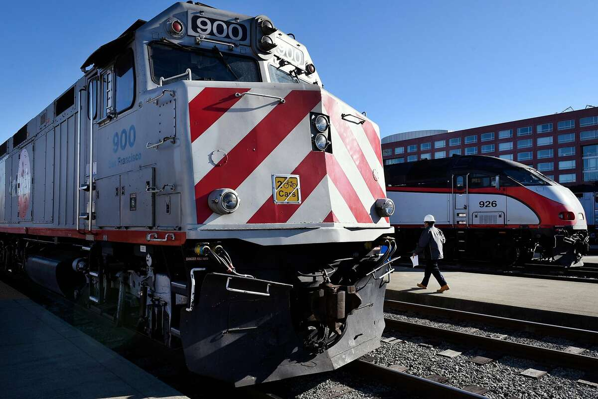 A CalTrain worker walks along the platform between two trains at the CalTrain Station in San Francisco, Calif., on Thursday December 21, 2017.