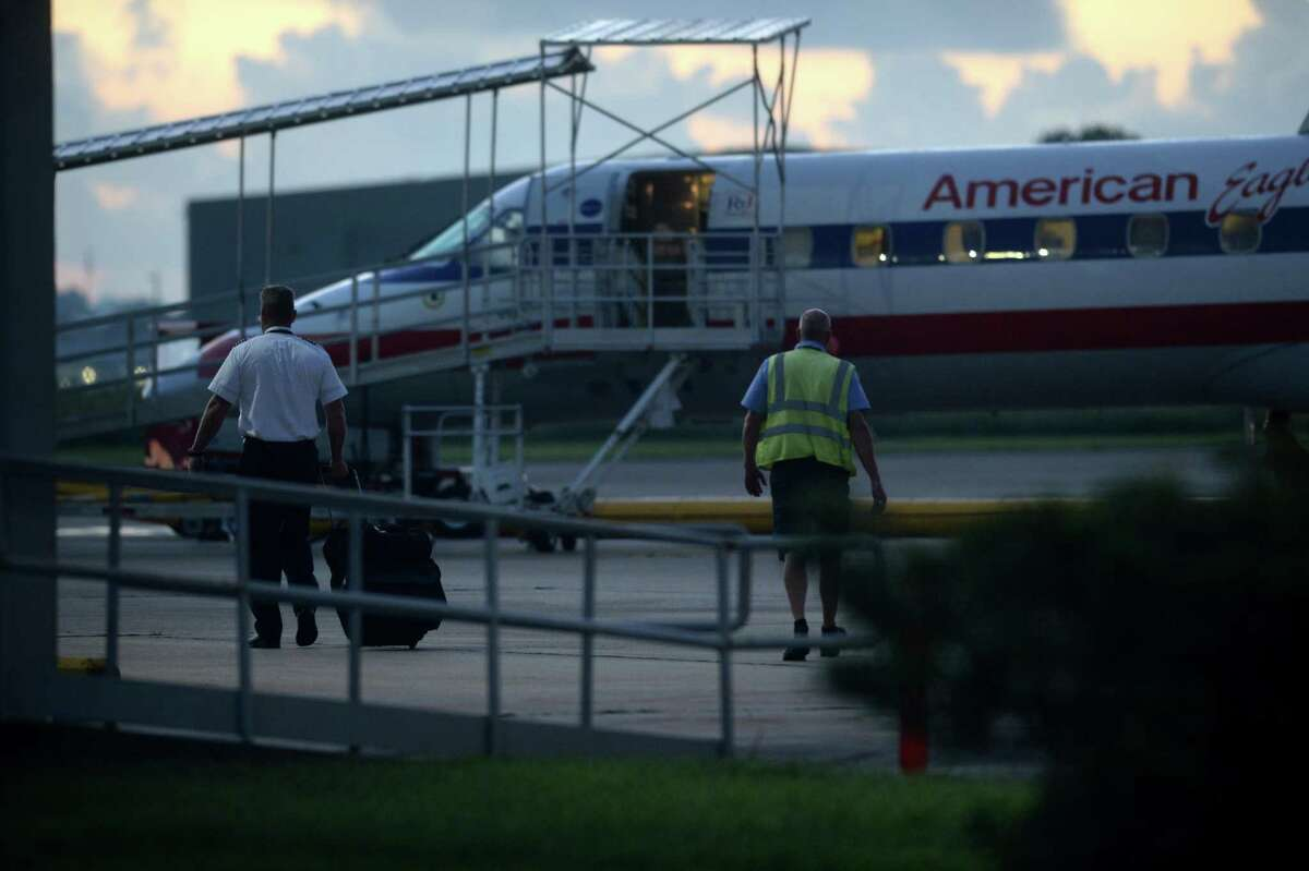 A crew member walks toward an American Airlines plane at the Jack Brooks Regional Airport early Thursday morning. In recent weeks, several passengers were bumped from their flight due to the weight limitations of using the airport?•s shorter, secondary runway. Construction on the primary runway was finished Tuesday and regular traffic is expected to continue. Photo taken Thursday, September 22, 2016 Guiseppe Barranco/The Enterprise