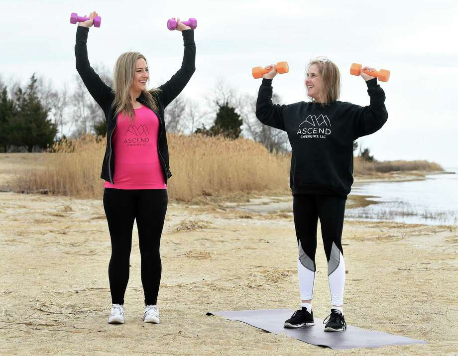 Former New England Patriot cheerleader and owner of Ascend Experience, Alex Brandy, demonstrates a dumb bell exercise with Lisa Zaccagnini of Beacon Falls at the Clinton Town Beach on March 12, 2020. Photo: Arnold Gold / Hearst Connecticut Media / New Haven Register