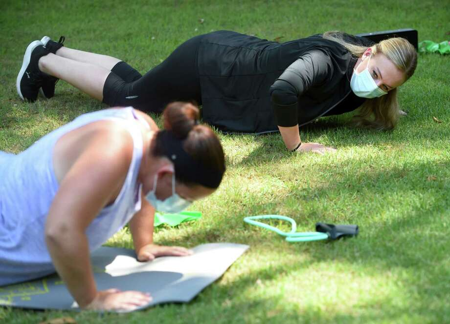 Personal trainer Alex Brandy, right, does pushups with Lindsay Stopa in Stopa's front yard in Clinton on July 20. Brandy is a former New England Patriot cheerleader and owner of Ascend Experience.