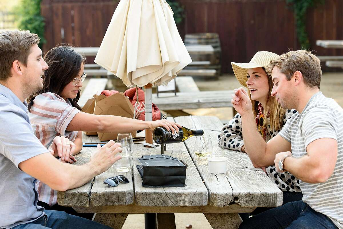 Conor and Paige McLaughlin, left, and Pete Horn and Laurie Moot sip wine in a picnic area at Imagery Estate Winery in Glen Ellen, Calif, on Sunday November 11, 2018.