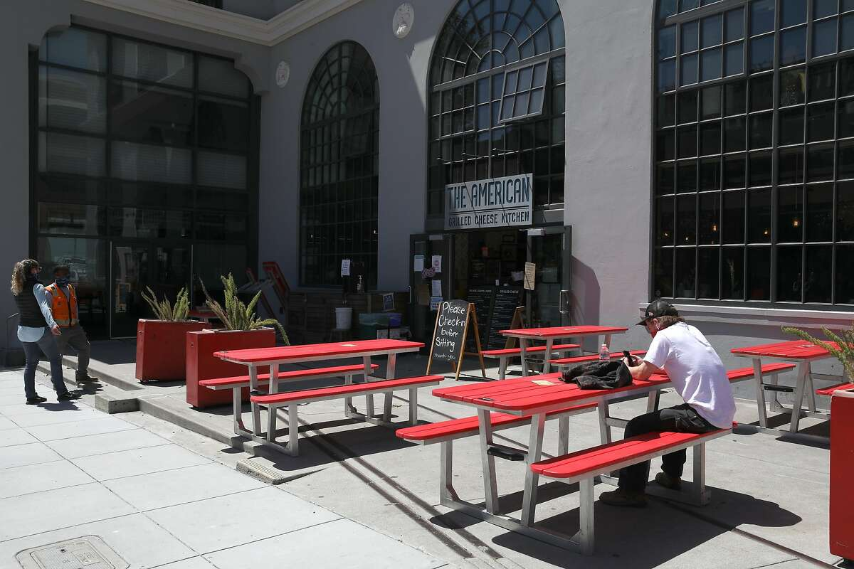 Customers wait for their orders near outdoor seating at The American Grilled Cheese Kitchen on Tuesday, July 7, 2020, in San Francisco, Calif. Mayor London Breed may announce a change of plans on indoor dining in SF.