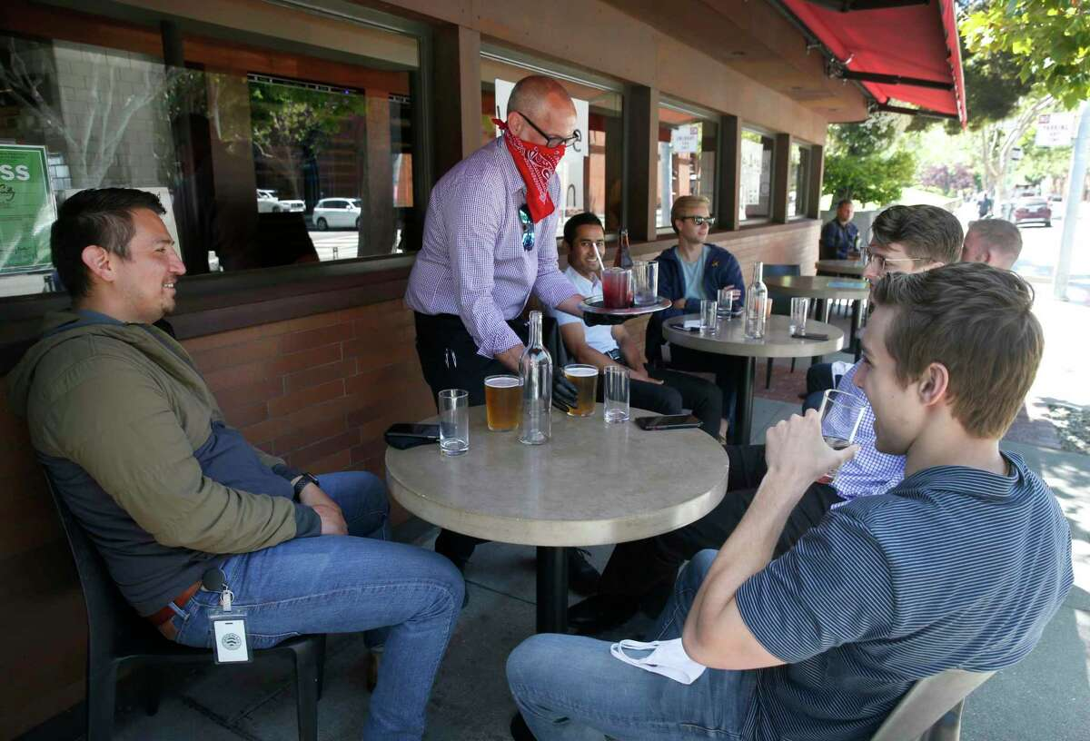 Mike Mendez-Gatewood serves a group outdoors at Fog City Diner in San Francisco.